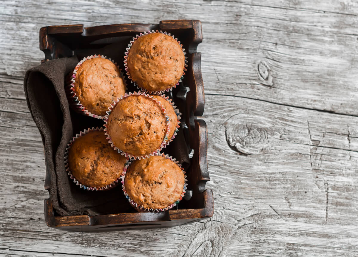 overhead view of oatmeal muffins in a rustic wooden crate with a brown napkin