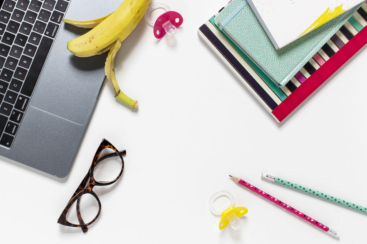 flatlay laptop, eyeglasses, banana, pencils, pacifier, and notebooks. Back to school stress for working moms