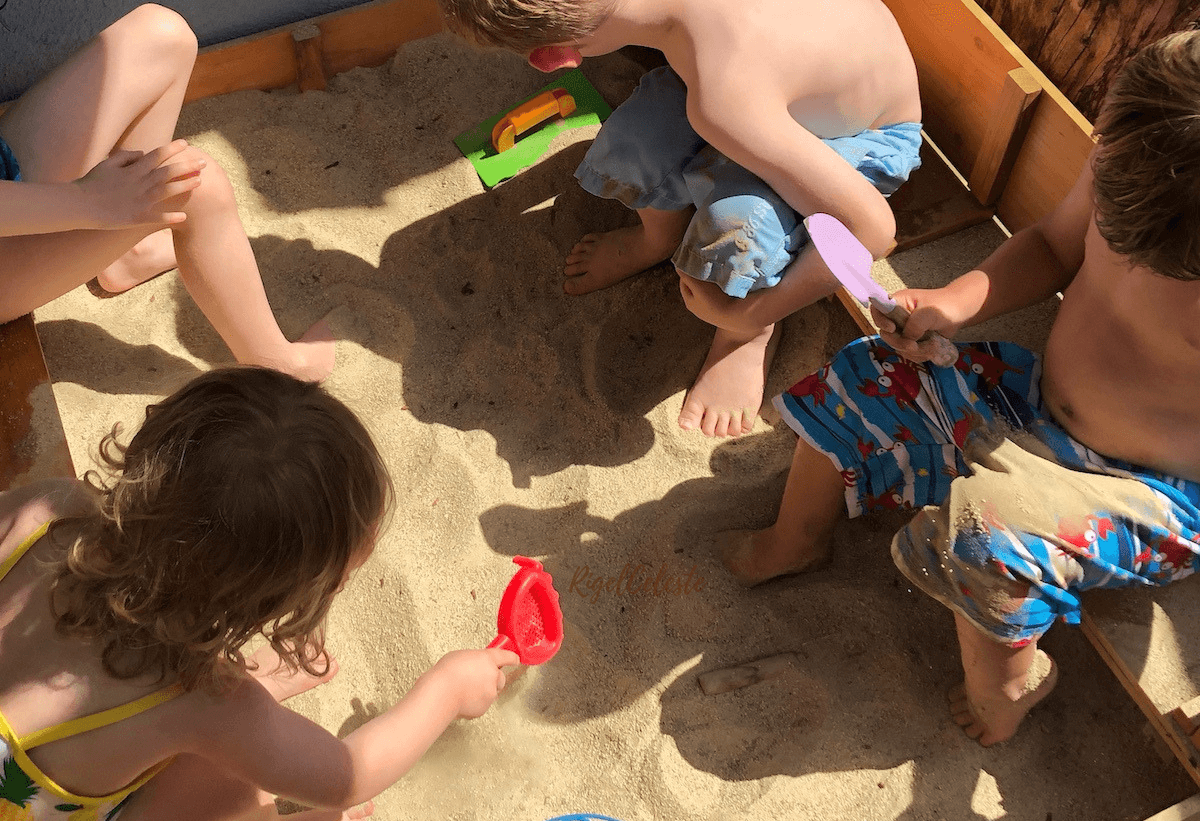 young kids playing outside in sandbox